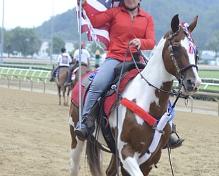 Katie Rickman    The Vindicator.An outrider pony walks the track with a rider displaying the flag prior to the start of the West Virginia Derby August 2, 2014.