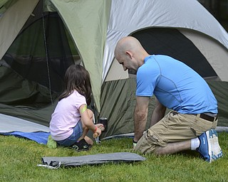 Katie Rickman | The V indicator.Peyton Arn, 4 of Boardman helps her father Ben Arn put their tent up at Family Camp at Mill Creek MetroPark August 9, 2014.