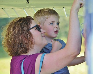 Jeff Lange | The Vindicator  Sondra Blankenhorn-Cook of Fort Wayne Indiana shows her son Ethan Cook (8) the inside of a plane on display during the Wings and Wheels Fundraiser event held on Saturday at the Ernie Hall Aviation Museum in Warren.