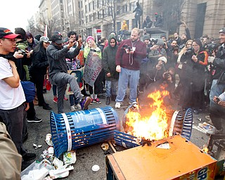 Protesters burn trash cans during the demonstration downtown Washington, Friday, Jan. 20, 2017, during the inauguration of President Donald Trump. ( AP Photo/Jose Luis Magana)