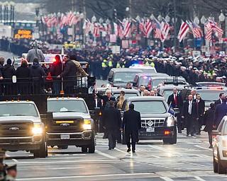 President Donald Trump and his wife Melania, center, walk during the Inaugural Parade on Pennsylvania Avenue, in Washington, Friday, Jan. 20, 2017. (AP Photo/Cliff Owen)