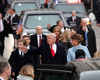 President Donald Trump, his wife Melania Trump and son Barron Trump walk along the inauguration day parade route in Washington, Friday, Jan. 20, 2017, after he was sworn in as the 45th president of the United States. (AP Photo/Carolyn Kaster)