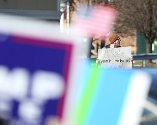 """Daniel Thomas, 22, of Austintown holds a """"Hate won't make us great"""" sign across the street from supporters of President Donald Trump as they hold flags and signs at the Summitville Tile parking lot on 224, Saturday, March 4, 2017 in Boardman. ..(Nikos Frazier   The Vindicator).."""