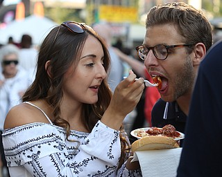 Matthew Melito takes a bite of girlfriend Sarina Mauerman's cavatelli dinner during the Greater Youngstown Italian Festival, Saturday, August 5, 2017 in Downtown Youngstown...(Nikos Frazier | The Vindicator)