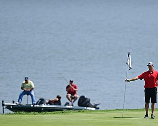 POLAND, OHIO - AUGUST 20, 2017: Jeff Rust holds the flag on the 9th hole, while fishermen fish in the lake behind him, during the final round of the Vindy Greatest Golf Tournament, Sunday afternoon at the Lake Club. DAVID DERMER | THE VINDICATOR