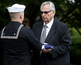 HM2 Todd Bollinger presents the flag that was draped over former state Sen. Harry Meshel's casket to a family member, Sept. 9, 2017, at Belmont Park Cemetery in Youngstown...(Nikos Frazier | The Vindicator)