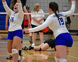 HUBBARD, OHIO - SEPTEMBER 12, 2017: Hubbard's Kristin Fahndrich, left, and Cailey Tingler celebrate after a Hubbard point during their match, Tuesday night at Hubbard High School. DAVID DERMER | THE VINDICATOR..Canfield's Morgan Cleevely picks herself up off the ground behind.