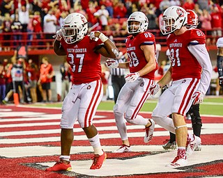 University of South Dakota running back Kai Henry (37) celebrates scoring a touchdown on Youngstown State during the first half at the DakotaDome on Saturday, Oct. 7, 2017 in Vermillion, S.D.