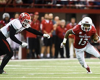 University of South Dakota wide receiver Shamar Jackson (13) jukes past a Youngstown State defender after a reception during the first half at the DakotaDome on Saturday, Oct. 7, 2017 in Vermillion, S.D.
