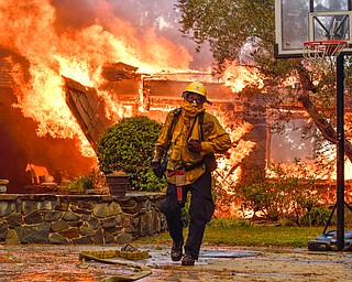 Firefighters work to extinguish a fire at a home as they battle a wildfire in Anaheim Hills, Calif., Monday, Oct. 9, 2017. Wildfires whipped by powerful winds swept through Northern California sending residents on a headlong flight to safety through smoke and flames as homes burned. (Jeff Gritchen/The Orange County Register via AP)