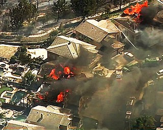 In this image made from a video provided by KABC-TV, a fire burns in the Anaheim Hills area of Anaheim, Calif., in northern Orange County in Southern California on Monday, Oct. 9, 2017. Wildfires whipped by powerful winds swept through Northern California sending residents on a headlong flight to safety through smoke and flames as homes burned. (KABC-TV via AP)
