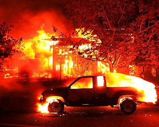 Coffey Park homes burn early Monday Oct. 9, 2017 in Santa Rosa, Calif. More than a dozen wildfires whipped by powerful winds been burning though California wine country. The flames have destroyed at least 1,500 homes and businesses and sent thousands of people fleeing. (Kent Porter/The Press Democrat via AP)
