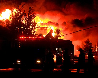Gold Fidge firefighters use a deck gun to protect structures in Coffey Park in Santa Rosa, Calif., Monday Oct. 9, 2017. More than a dozen wildfires whipped by powerful winds been burning though California wine country. The flames have destroyed at least 1,500 homes and businesses and sent thousands of people fleeing. (Kent Porter/The Press Democrat via AP)