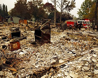 Firefighters drive through the Coffey Park area of Santa Rosa, Calif., looking for hotspots on Tuesday, Oct. 10, 2017. An onslaught of wildfires across a wide swath of Northern California broke out almost simultaneously then grew exponentially, swallowing up properties from wineries to trailer parks and tearing through both tiny rural towns and urban subdivisions. (AP Photo/Ben Margot)