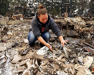 Gina Baier looks for family heirloom china that may have survived in the remains of her home in the Coffey Park area of Santa Rosa, Calif., on Tuesday, Oct. 10, 2017. An onslaught of wildfires across a wide swath of Northern California broke out almost simultaneously then grew exponentially, swallowing up properties from wineries to trailer parks and tearing through both tiny rural towns and urban subdivisions. (AP Photo/Ben Margot)