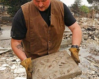 Luke Baier holds a block of concrete that he and his brothers left their handprints on as children which survived the fire in the Coffey Park area of Santa Rosa, Calif., on Tuesday, Oct. 10, 2017. An onslaught of wildfires across a wide swath of Northern California broke out almost simultaneously then grew exponentially, swallowing up properties from wineries to trailer parks and tearing through both tiny rural towns and urban subdivisions. (AP Photo/Ben Margot)