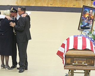 William D Lewis The vindicator Girard PD chief John Norman embraces slain officer Justin Leo's parent's Dave and Pat Leo during funeral services at YSU Beegley Center 10292017.