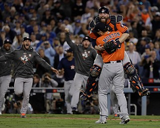 Houston Astros catcher Brian McCann leaps in the arms of starting pitcher Charlie Morton after Game 7 of baseball's World Series against the Los Angeles Dodgers Wednesday, Nov. 1, 2017, in Los Angeles. The Astros won 5-1 to win the series 4-3. (AP Photo/Matt Slocum)