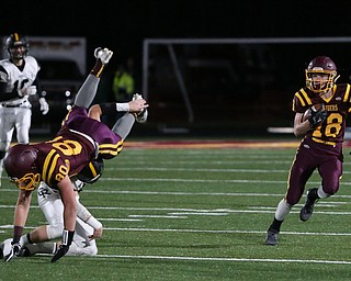South Range's Mathias Combs(18) runs the ball as South Range's Jacob Gehring(80) is flipped over by Crestview's Chucky Lindsay(51) during the first quarter as Crestview High School takes on South Range High School, Friday, Nov. 3, 2017, at Raider's stadium at the Rominger Sports Complex in Canfield...(Nikos Frazier | The Vindicator)..