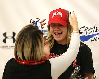 Adria Powell cringes as her mom, Olivia Powell, adjusts her Ohio State hat, after Adria signed her letter of intent to attend Ohio State University and play volleyball, Wednesday, Nov. 8, 2017, in the Hubbard High School Gymnasium in Hubbard. ..(Nikos Frazier | The Vindicator)