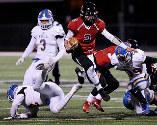 WARREN, OHIO - NOVEMBER 10, 2017:  Canfield's Vinny Fiorenza (2) leaps over NDCL Matt Tuohey (2) as he gains a 1st down  during the 1st qtr. at Harding High School, Mollenkopf Stadium.  MICHAEL G TAYLOR | THE VINDICATOR
