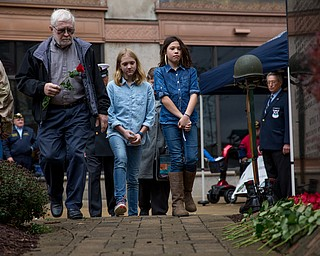 Rebecca Devereaux | The Vindicator ..Bill Douglas carries a rose to place on the Vietnam Memorial in memory of his brother Tom Douglas during the annual laying of the rose ceremony in downtown Youngstown on Sunday. Douglas walks with his grandchildren Afton Douglas, 9 (center), Zoey Douglas, 11 and his wife Sharon Douglas of New Middletown pictured behind.