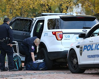 A police officer watches as a paramedic tends to a man after an apparent assault, Monday, Nov. 6, 2017, at the Covington St. and Broadway St. in Youngstown...(Nikos Frazier | The Vindicator)