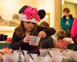 Sarah Marovich, 6 of Boardman scoops some sprinkles for decorating her cookie at the Butler Family Fun Day at the Butler Institute of American Art on Sunday in Youngstown.