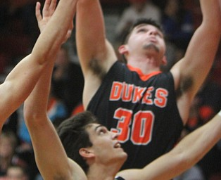 William D Leiws the vindicator Canfield's Spencer Woolley(11) pulls  down a rebound past Marlingtons Austin Brady(30) during 11302017 action at Canfield.