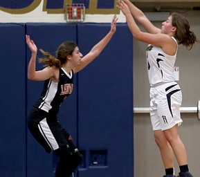 Lowellville's Maddie Kelly (3) goes up for three as Mineral Ridge's Kalyn Stricklin (2) attempts to block her shot during the fourth quarter as Mineral Ridge High School takes on Lowellville High School, Monday, Dec. 4, 2017, at Lowellville High School in Lowellville. Mineral Ridge won 45-33...(Nikos Frazier | The Vindicator)..