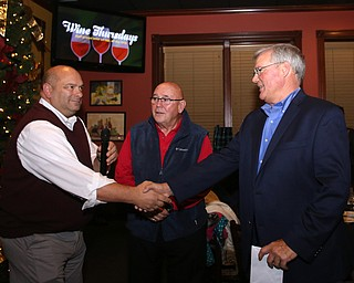 Trustee Larry Moliterno shakes Boardman Police Chief Jack Nichols' hand during a retirement party honoring   Chief Nichols, Wednesday, Dec. 6, 2017, at Magic Tree Pub & Eatery in Boardman. Chief Nichols will officially retire on December 31, after having served 40 years with the Boardman Police Department...(Nikos Frazier | The Vindicator)