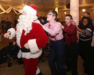 Santa leads the conga line during the 13th annual Winterfest special needs dance, Wednesday, Dec. 6, 2017, at the Mahoning Country Club in Girard...(Nikos Frazier | The Vindicator)