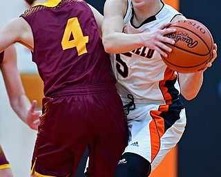 NEW MIDDLETOWN, OHIO - DECEMBER 29, 2017: Springfield's Clay Medvec secures the basketball while colliding with South Range's Brennan Troy during the first half of their game on Friday night at Springfield High School. DAVID DERMER | THE VINDICATOR