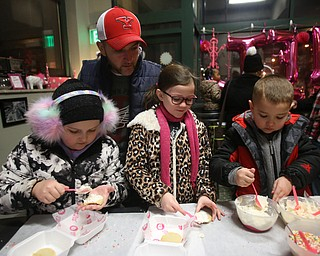 Jim Johnstone of Boardman(YSU hat) watches as his kids(from left), Ryley(10), Hayley(8) and Brayden(5) decorate cookies during First Night Youngstown, Sunday, Dec. 31, 2017, at One Hot Cookie in Youngstown. ..(Nikos Frazier | The Vindicator)