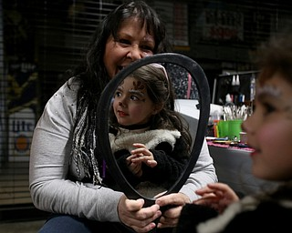 Ariana McDonough(5) of Canfield gets a reindeer face painted by Maria Jones of New Castle during First Night Youngstown, Sunday, Dec. 31, 2017, at LOCATION in Youngstown. ..(Nikos Frazier | The Vindicator)