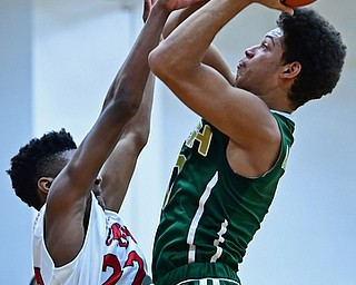 WARREN, OHIO - JANUARY 2, 2017: Ursuline's Ryan Clark goes to the basket against JFK's Ethan Courtney during the first half of their game on Tuesday night at Warren JFK High School. DAVID DERMER | THE VINDICATOR