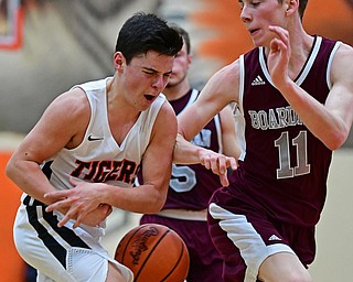 HOWLAND, OHIO - JANUARY 5, 2018: Howland's Frank Rappach loses control of the ball while driving on Boardman's Billy Cammack during the second half of their game, Friday night at Howland HigH School. DAVID DERMER | THE VINDICATOR