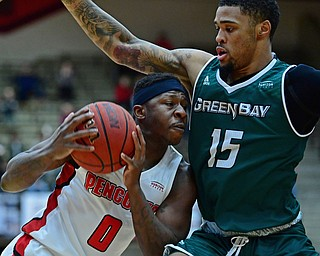YOUNGSTOWN, OHIO - JANUARY 6, 2017: Youngstown State's Tyree Robinson drives on Green Bay's Manny Patterson during the first half of their game, Saturday night at Beeghly Center. DAVID DERMER | THE VINDICATOR