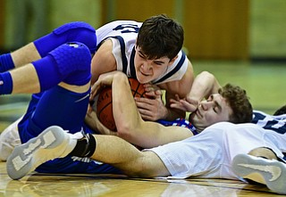 McDONALD, OHIO - JANUARY 9, 2018: Western Reserve's Cole DeZee attempts to secure the ball while laying on top of McDonald's Josh Celli while Zack Rasile attempts to rip the ball free during the second half of their game, Tuesday night at McDonald High School. DAVID DERMER | THE VINDICATOR