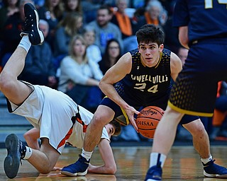 NEW MIDDLETOWN, OHIO - FEBRUARY 2, 2018: Lowellville's Joe Ballone protects the ball while looking to pass after Springfield's Drew Clark dove in an attempt to knock the ball away during the first half of their game on Friday night at Springfield High School. DAVID DERMER   THE VINDICATOR