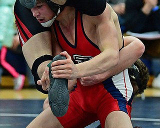 AUSTINTOWN, OHIO - FEBRUARY 3, 2018: Fitch's Gus Sutton controls the foot of Girard's Alex Delgarbino as he clings to his back during their 126lb EOWL Championship bout, Saturday night at Austintown Fitch High School. DAVID DERMER   THE VINDICATOR