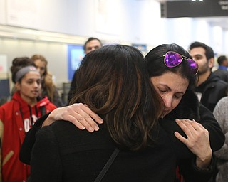 Fidaa Mushleh(back) hugs Amal Saleh goodbye before departing for her flight to reunite with her husband, Al Adi in Amman, Jordan, Wednesday, Feb. 7, 2018, at Cleveland Hopkins International Airport in Cleveland. Adi was deported to Jordan last week after 13 days in ICE detainment...(Nikos Frazier | The Vindicator)