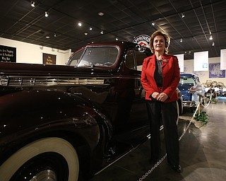 Executive Director Mary Ann Porinchak poses for a photo next to a 1940 One-Ten Touring Sedan Model 1800, Wednesday, Jan. 24, 2018, at the Packard Museum in Warren...(Nikos Frazier | The Vindicator)