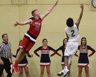 Ursuline guard DeShawn Harris (2) hooks a layup as Austintown Fitch center Nick Belcik (32) reaches out in an attempt to block his shot in the first quarter of an OHSAA high school basketball game, Tuesday, Feb. 13, 2018, in Youngstown. Ursuline won 63-58...(Nikos Frazier | The Vindicator)