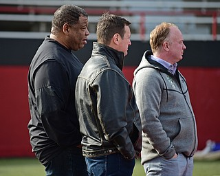YOUNGSTOWN, OHIO - FEBRUARY 18, 2018: Kentucky head coach Mark Stoops, right, Kentucky assistant coach Vince Marrow, left, and former Oklahoma head coach Bob Stoops stand on the sideline during the Youngstown State practice on Sunday afternoon at Stambaugh Stadium. DAVID DERMER | THE VINDICATOR