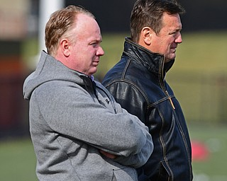 YOUNGSTOWN, OHIO - FEBRUARY 18, 2018: Kentucky head coach Mark Stoops and former Oklahoma head coach Bob Stoops stand on the sideline during the Youngstown State practice on Sunday afternoon at Stambaugh Stadium. DAVID DERMER | THE VINDICATOR