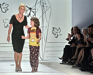 Following the showing of her 2008 spring collection, fashion designer Nanette Lepore reacts to applause as she walks with her daughter Violet Savage on the runway, during Fashion Week in New York, Monday Sept. 10, 2007.