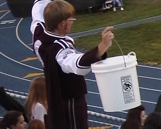 Spartan Band Member Standing holding his instrument in the air.
