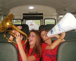 Fitch Varsity Cheerleaders, Sara McAllister and Britny Benett, belt out all the right notes as they prepare to cheer on the football team while riding the bus to their game in Jackson
