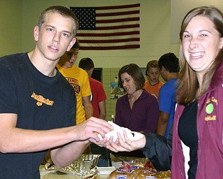 Student Council member Trevor Shively serves Autumn Carter hotdogs at the Tailgate pep rally.